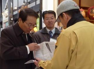 21日、松山市の商店街で「提言」を説明する笹岡さん(左端)