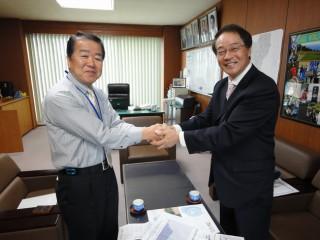 芸西村長の竹内勉町長と握手する笹岡さん(右)